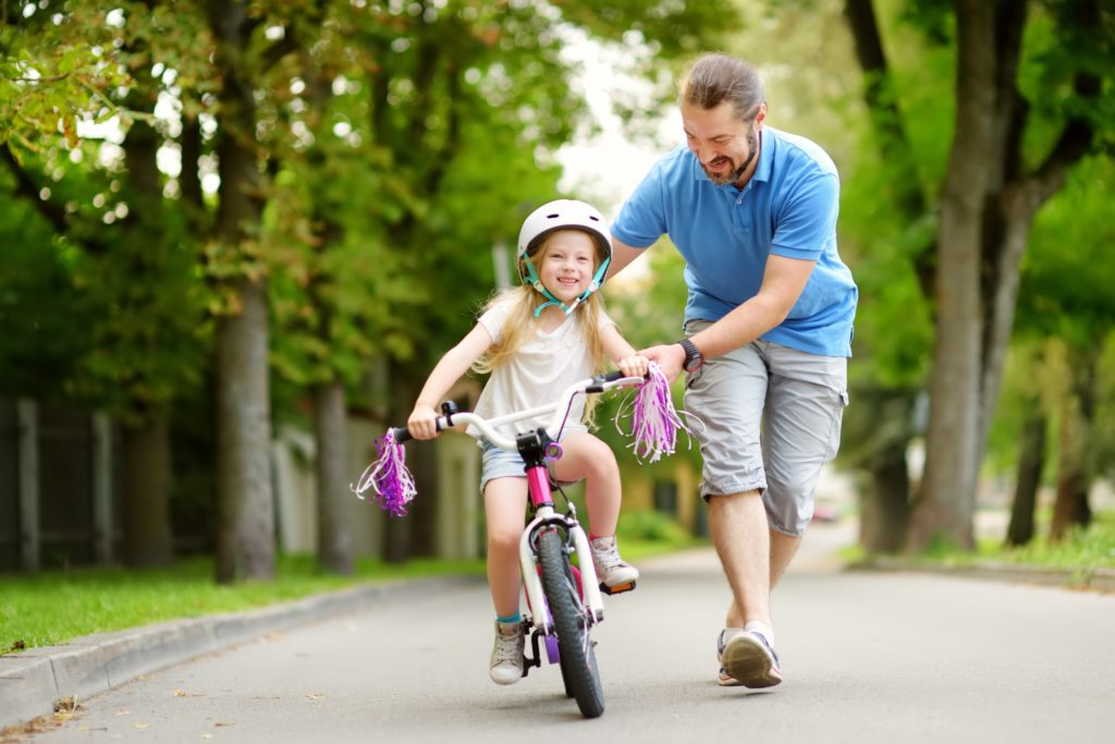 Happy father teaching his little daughter to ride a bicycle