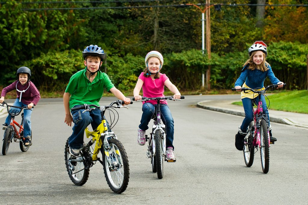 A group of happy children safely riding their bicycle on the street while wearing a helmet